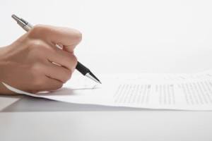 Woman's hand signing documents