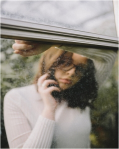 picture of girl on phone behid dirty window