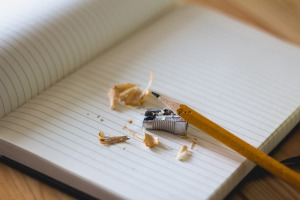 Pencil with sharpener, pencil shavings and blank notebook
