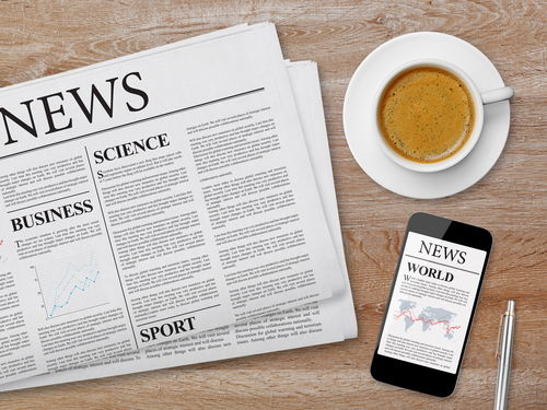 News page on tablet, newspaper and coffee