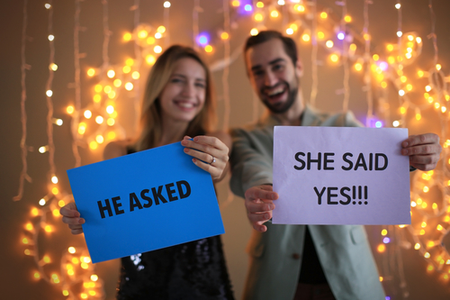 Happy couple holding papers with text HE ASKED and SHE SAID YES against blurred lights on engagement day