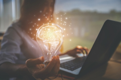 creative idea. Concept of idea and innovation, woman at laptop top holding illuminated lightbulb in her hand